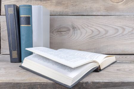 The unwrapped book lies on a wooden shelf against the background of standing books