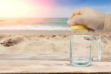 Hand squeezed lemon juice into a glass against the background of the sea and the beach Reklamní fotografie