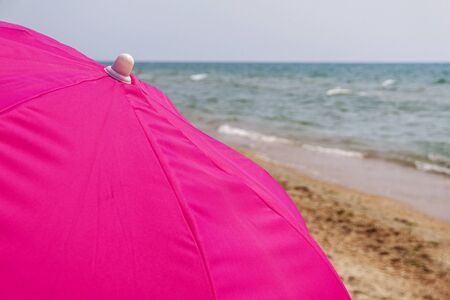 The upper part of the umbrella against the sea and the sky