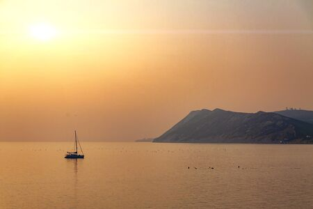 Sunset at sea, against the backdrop of boats and mountains.