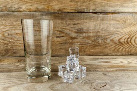 Empty glass with ice cubes on a wooden background Reklamní fotografie