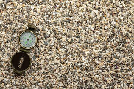 Travel concept, tourism. The compass lies on small stones Reklamní fotografie