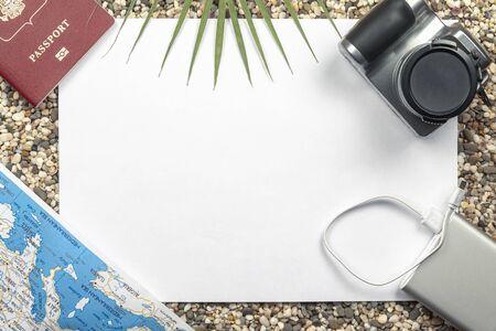 Travel concept. A camera, passport, card, powerbank lie on the beach