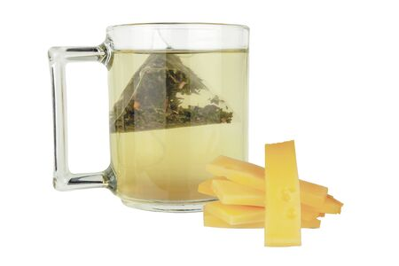 Slices of cheese lie next to a mug of green tea on a white background.