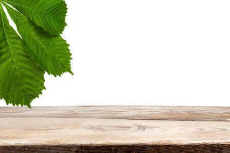 Chestnut leaves over wooden planks on a white background