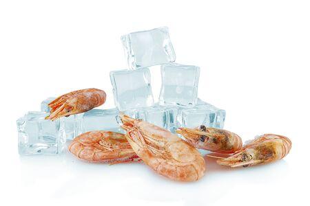 Frozen shrimp lie next to ice cubes on a white background Reklamní fotografie