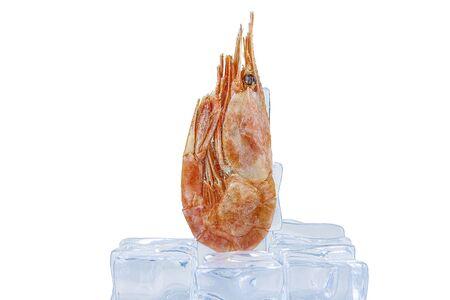 Frozen shrimp lies on ice cubes. On white background