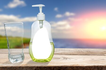 Glass cup with dishwashing detergent stand against the backdrop of nature