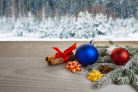 Christmas toys lie on the boards against the background of the winter forest