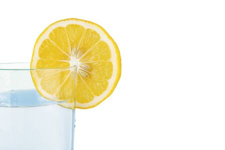A slice of lemon planted on the edge of a glass of water Foto de archivo
