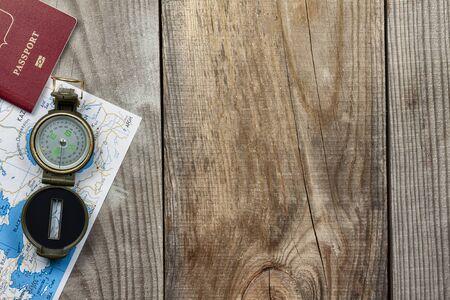 Travel Planning Concept. Compass, passport, map lie on a wooden background Foto de archivo
