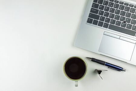The laptop keyboard is next to a coffee mug, a pen and a paper clip