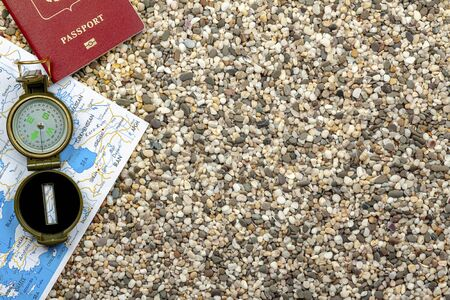 Travel Planning Concept. Compass, passport, map lie on the sand from the beach Foto de archivo
