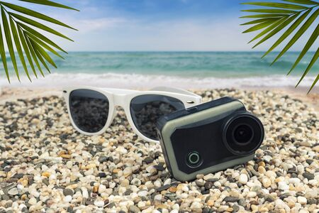 Sun goggles and action camera by the sea
