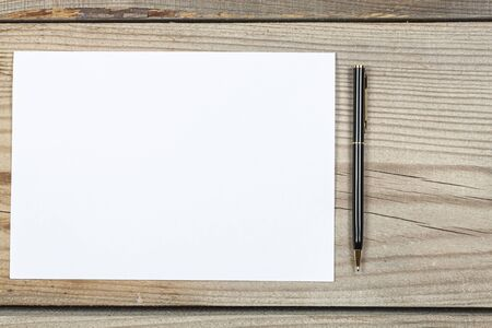 A template for text. A sheet of paper and a pen lie on a wooden background Foto de archivo