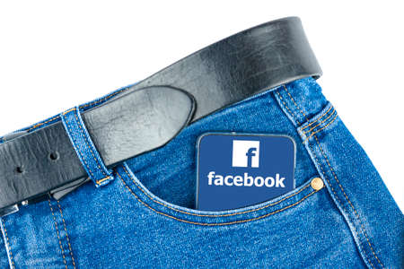 Russia Kaluga 03.07.2020 In the pocket of your trousers there is a phone with the logo of the Facebook social network.