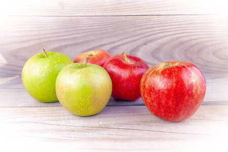 Red and yellow apples on wooden boards