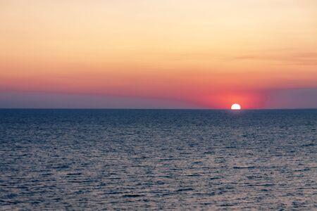 Evening sea against the setting sun over the horizon