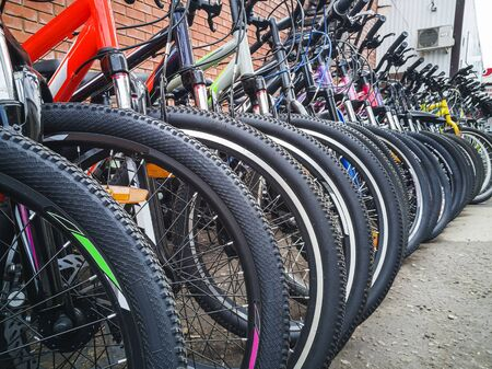 Bicycles stand in a row. Wheels close-up Foto de archivo