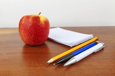 Apple fountain pen notepad lie on the table Foto de archivo