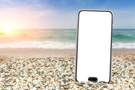 Phone with insulation on the beach and sea Foto de archivo