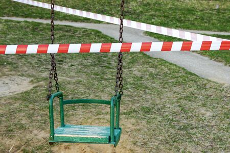 Self-isolation, a ban on walking. Childrens swings are closed, you cant ride. Foto de archivo - 145453762
