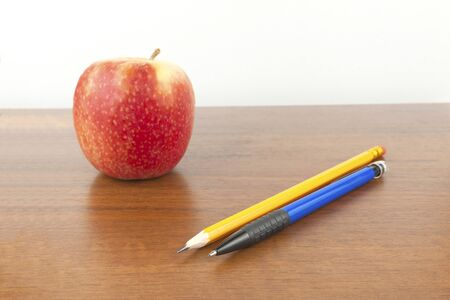 An apple with pencils is on the table, a white background
