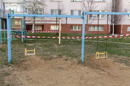 Self-isolation, a ban on walking. Childrens swings are closed, you cant ride. Foto de archivo - 145772820