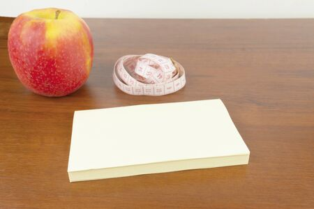 An apple, stickers, measuring tape, lie on the table