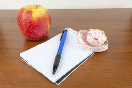 An apple, a notebook, a measuring tape, a pencil lie on a table.