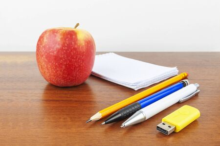 An apple, a notebook, pencils, a flash drive are on the table