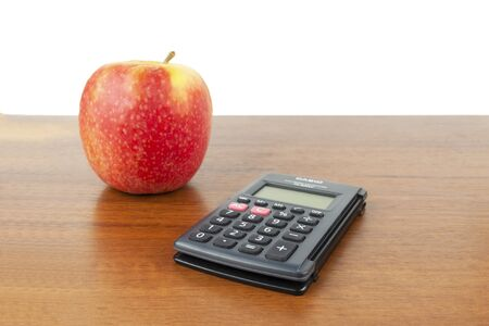 An apple, a calculator, pen, flash drive, notebook lie on the table Imagens