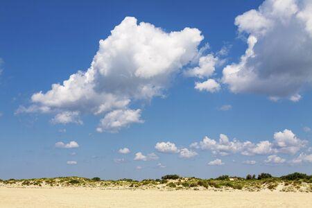 Cumulus clouds over sand hills