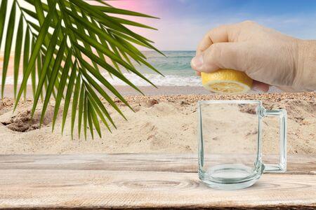 The hand squeezes the juice out of the lemon against the sea Foto de archivo
