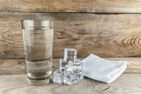 Glass with foda, next to ice cubes and a towel layer on a wooden background Foto de archivo - 147801939