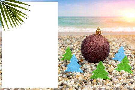 New Year by the sea. New Year's toy on the beach by the sea in the heating of paper Christmas trees