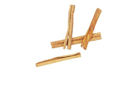 Three pieces of cinnamon lie on a white background, close-up Imagens