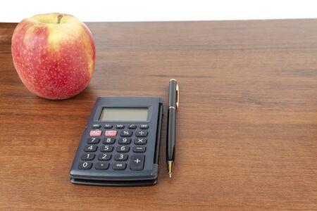 Apple calculator pen lie on the table.