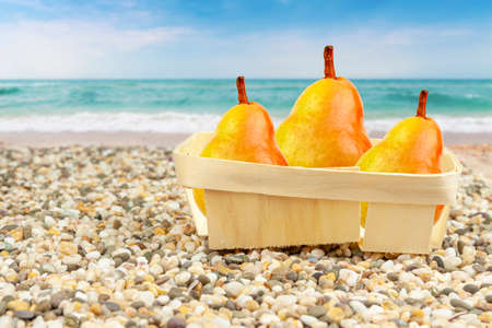 Pears in the package on a sandy beach.