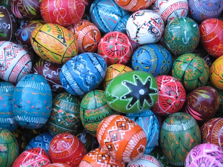 decorate: lots of wooden decorated easter eggs in various colors for sale in a winter market