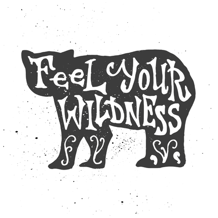 wildness: Lettering composition. Phrase Feel your wildness inscribed into bear silhouette. Ink splashes on white background.