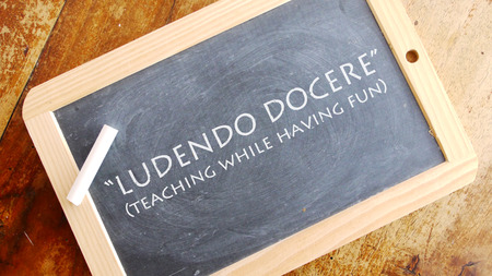 translated: Ludendo docere. Latin phrase, usually you translated into Inglese as teaching while having fun.
