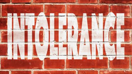 intolerancia: Intolerancia escrito en una pared de ladrillo.