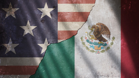 US and Mexico Flag on Cracked Concrete Wall With Shadow Gate Banco de Imagens