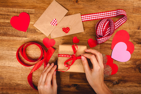 card making: Hearts, gift, ribbons, envepopes on wood background. Womans hands making handmade valentines day decoration Stock Photo