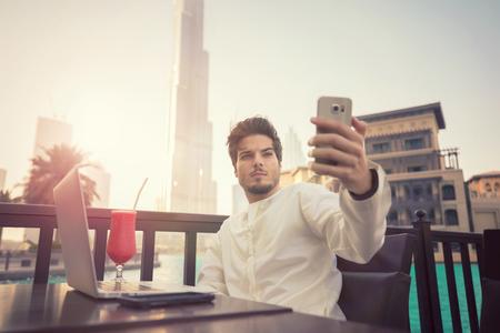 Arab young man taking selfie photo on smartphone wearing Kandura in Dubai