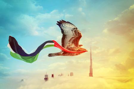 Halcón volando en el cielo de Dubai con la bandera de los Emiratos Árabes Unidos en el pico