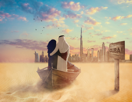Emirati couple sitting on boat crossing the Sahara to Dubai. Imagens