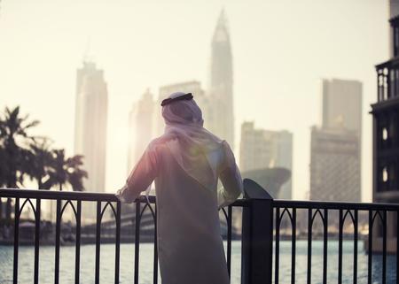 Arab man looking to Dubai skyline evening time