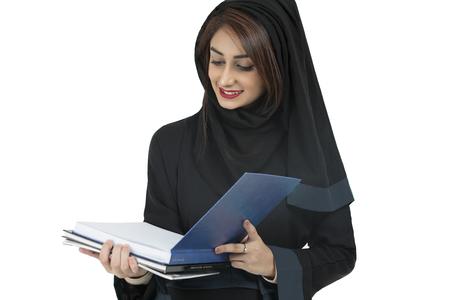Arabic student wearing abaya, holding blue book